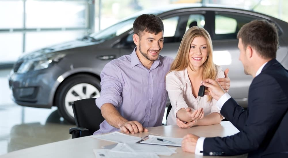 A happy couple is at a Cincinnati Chevy dealer discussing trade in value with a salesperson.