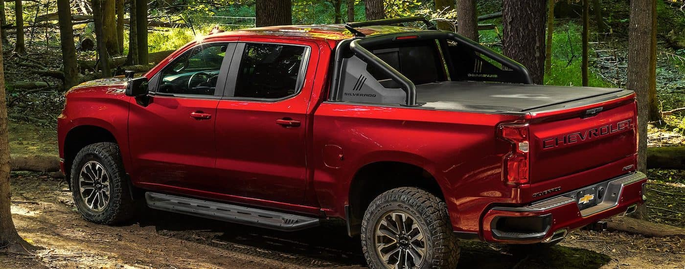 A red 2019 Chevy Silverado accessorized with a tonneau cover and roll bar