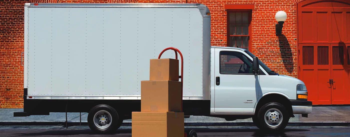 A white 2019 Chevy Cutaway box truck is getting loaded with boxes in front of bright red brick building in Cincinnati.