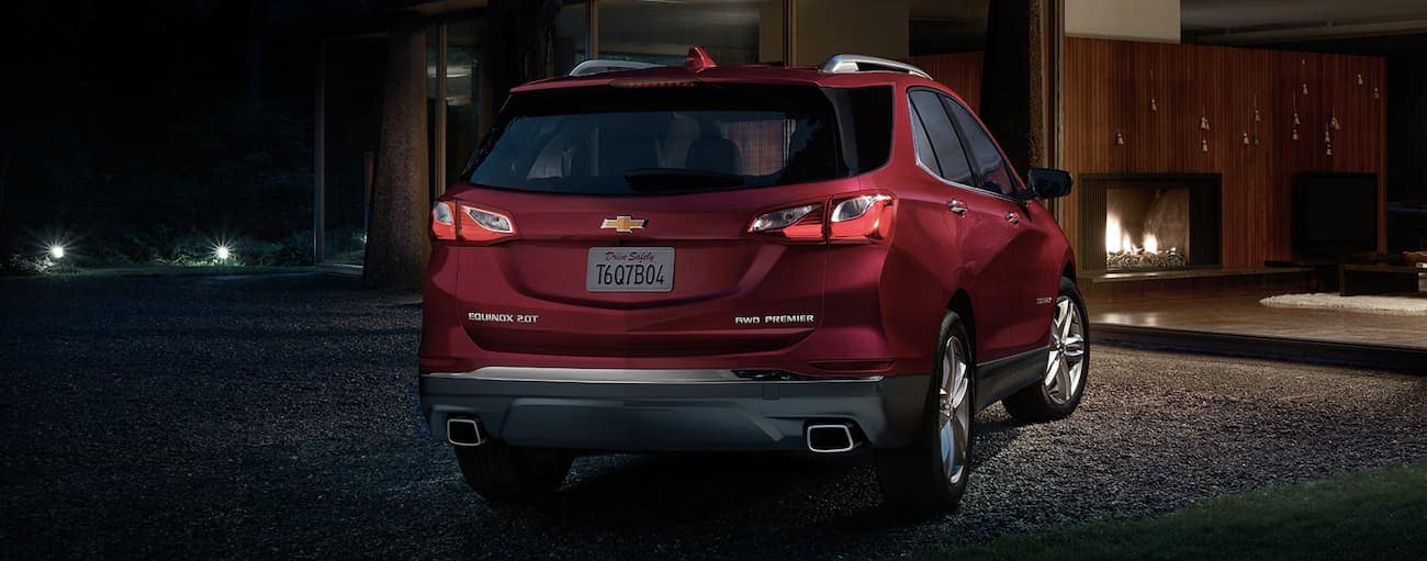 A red 2019 Chevy Equinox parked outside a modern upscale home