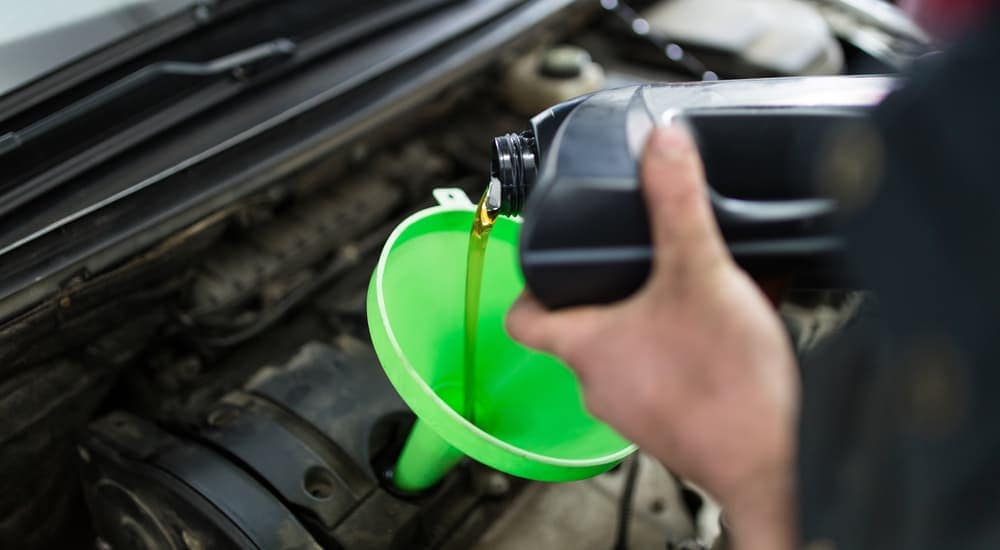 Pouring oil into a green funnel during an express oil change