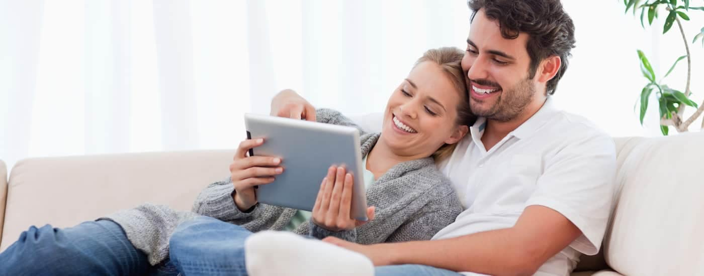 A young couple looks online at the inventory for used cars Columbus Ohio