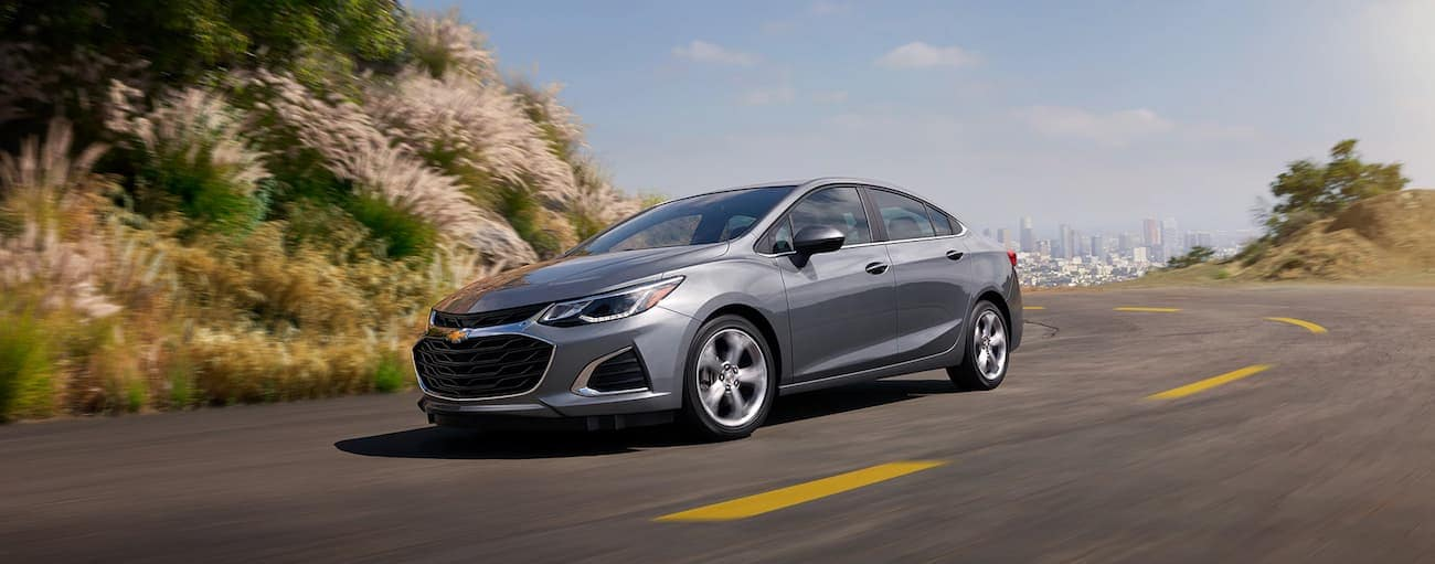 A gray 2019 Chevy Cruze driving away from a city