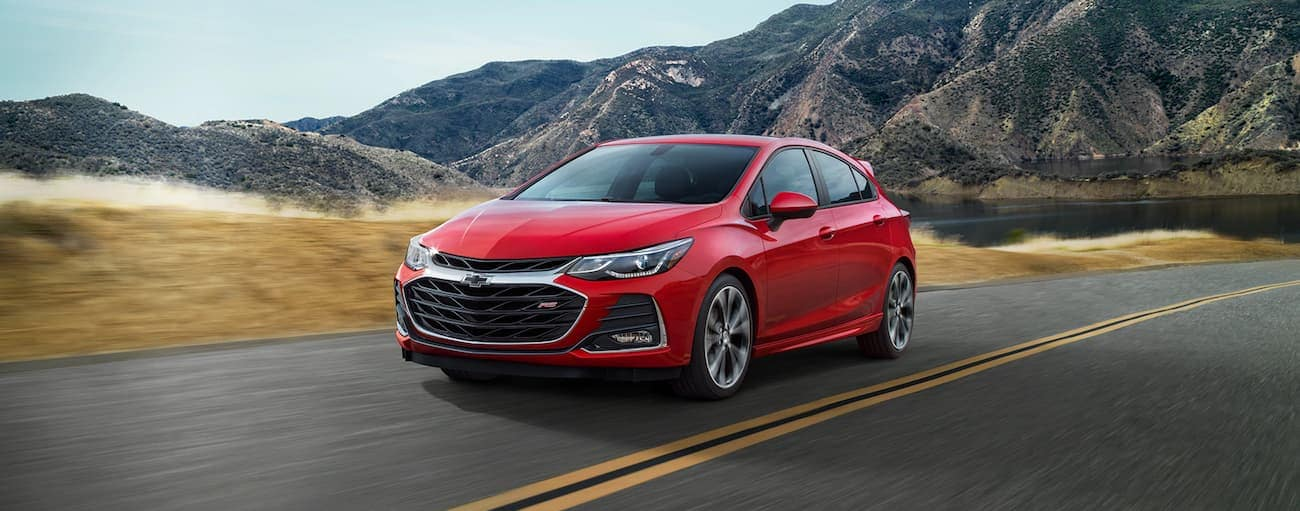 A red 2019 Chevy Cruze hatchback driving along a mountain road
