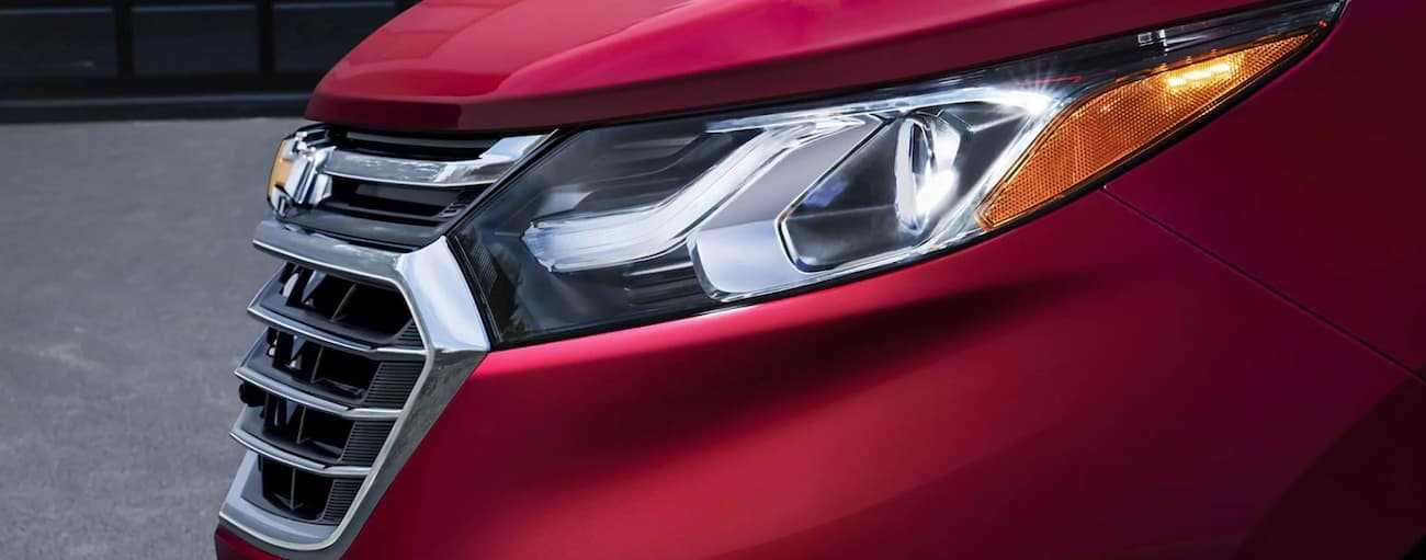 A closeup of the driver side headlight on a red 2019 Chevy Equinox
