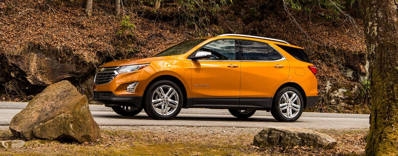 An orange 2019 Chevy Equinox driving in the woods