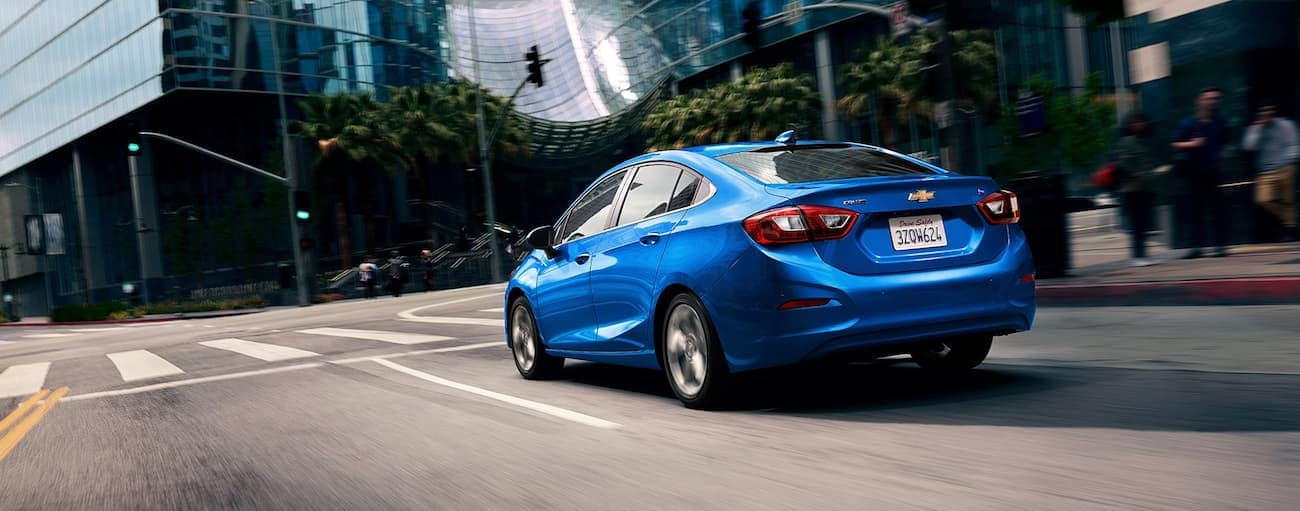 A blue 2019 Chevrolet Cruze driving down a city street. Check out entertainment when comparing the 2019 Chevy Cruze vs 2019 Mazda 3.