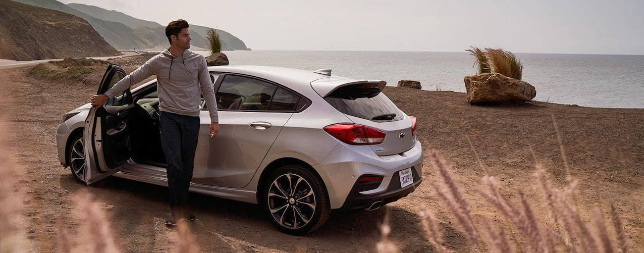 A man steps out of a silver 2019 Chevrolet Cruze hatchback at a beach