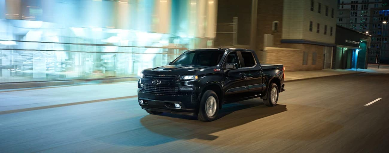 A black 2019 Chevy Silverado is driving downtown at night near Cincinnati, OH. Check out performance when comparing the 2019 Chevy Silverado vs 2019 Ram 1500.