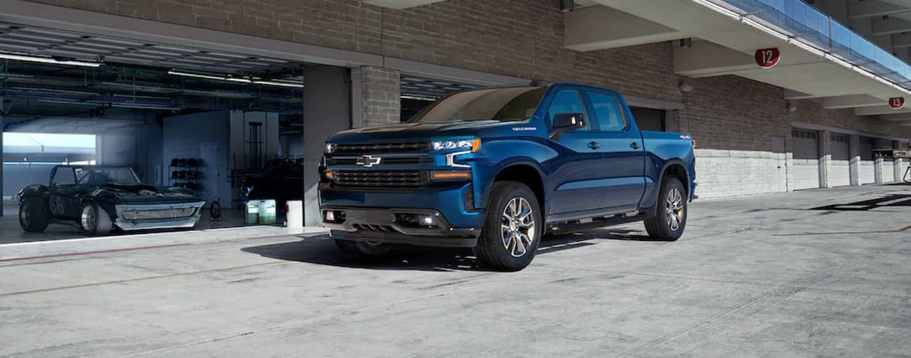 A blue 2019 Chevy Silverado is parked outside a mechanic pit garage with an older race car inside. Check out safety when comparing the 2019 Chevy Silverado vs 2019 Ram 1500 in Cincinnati, OH.