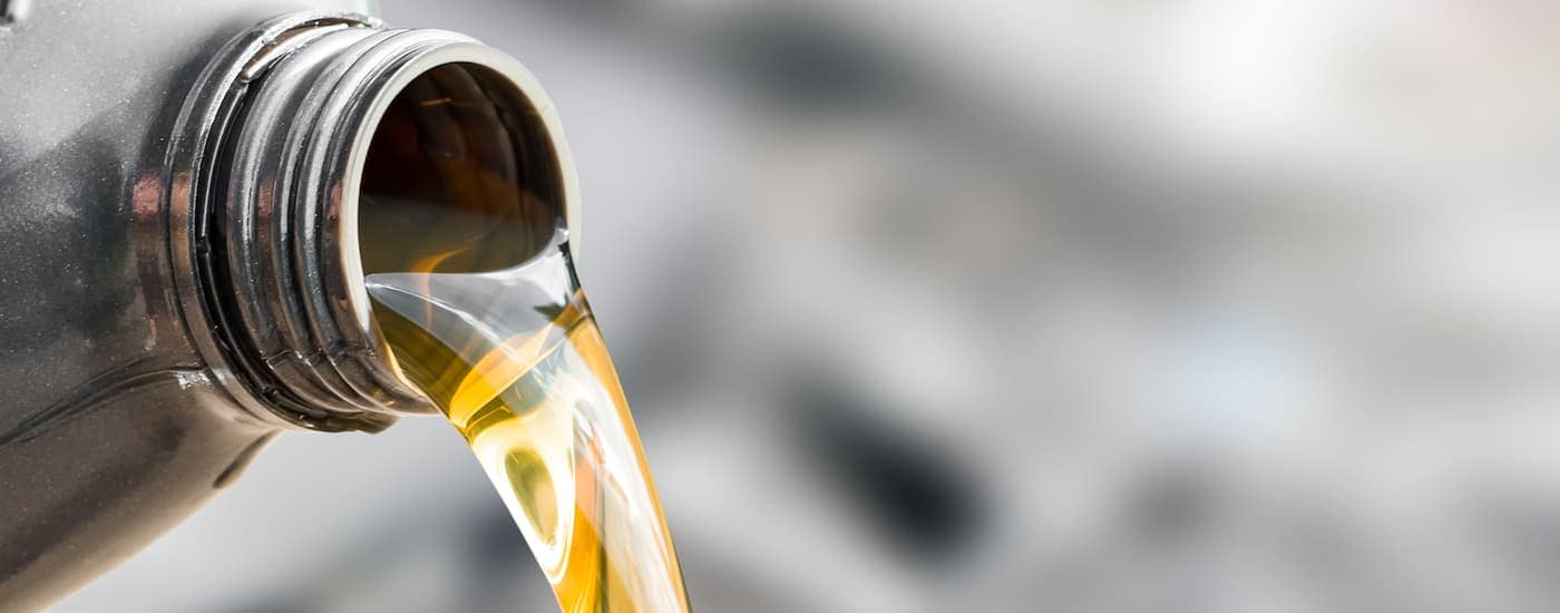 Oil is being poured from the mouth of the bottle in a closeup.
