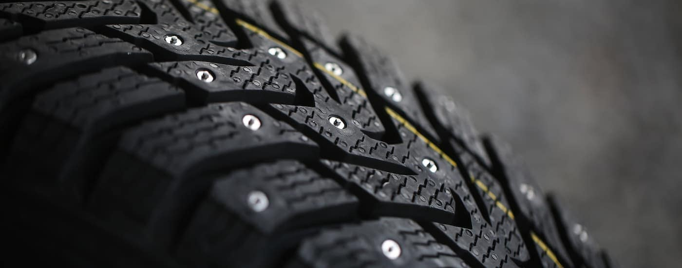 A close up of a studded winter tire is shown. With icy winters, snow tires in Cincinnati can be important.