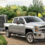 A landscaper is loading plants into a grey 2019 Chevy 2500 with an enclosed trailer attached.