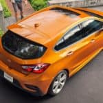 An orange 2017 Chevy Cruze hatch is shown parked from an above angle. Find used car values for this model to see what it is worth.