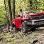 A red 2019 Chevy Colorado ZR2 Bison is climbing over rocks in the woods outside Cincinnati, OH.