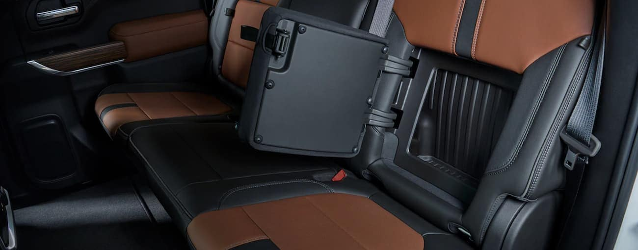 The black and tan interior in the 2019 Chevy Silverado is shown with a rear seat compartment open, which is a popular feature in Cincinnati, OH.