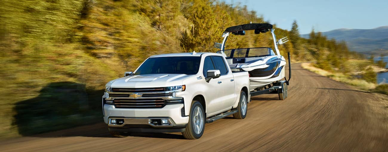 A white 2019 Chevy Silverado is towing a boat while on vacation from Cincinnati, OH. Check out price when comparing the 2019 Chevy Silverado vs 2019 GMC Sierra.