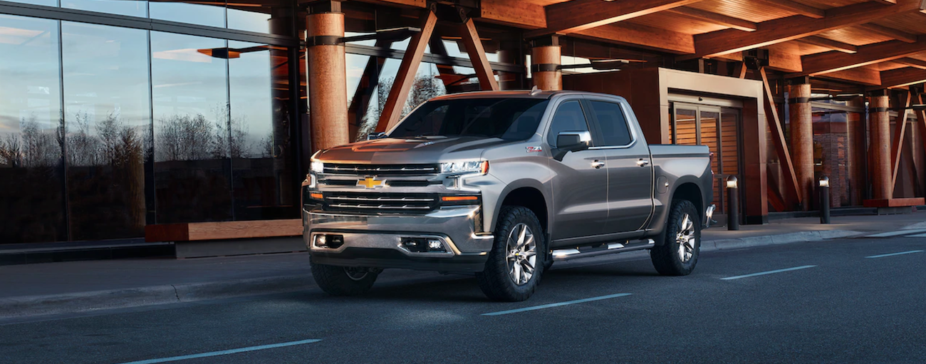 A silver 2019 Chevy Silverado is parked outside a glass and wood building at dusk near Cincinnati, OH.