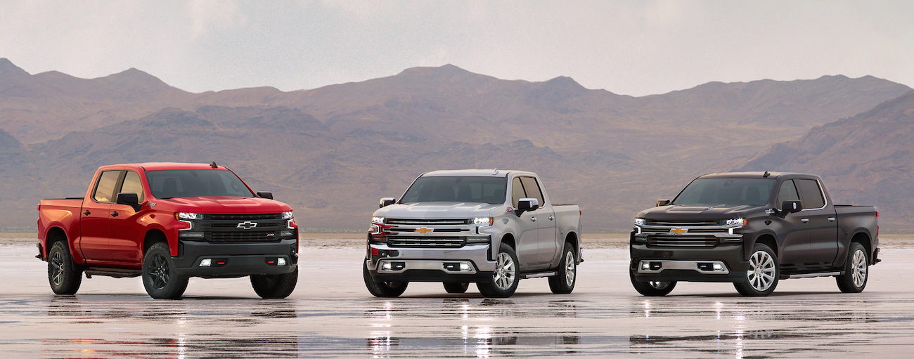Three 2019 Chevy Silverados of differing trims are parked with mountains in the background. Check out trim options when comparing the 2019 Chevy Silverado vs 2019 Nissan Titan - Cincinnati, OH.