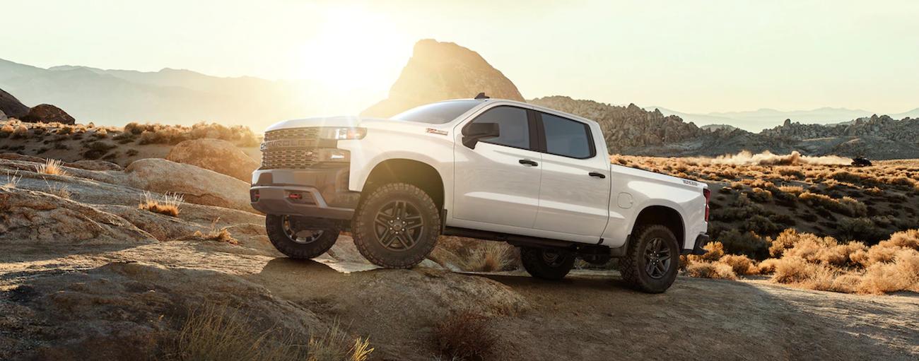 A white 2019 Chevy Silverado is off road in the desert at sunrise. Check out engine options when comparing the 2019 Chevy Silverado vs 2019 Nissan Titan - Cincinnati, OH