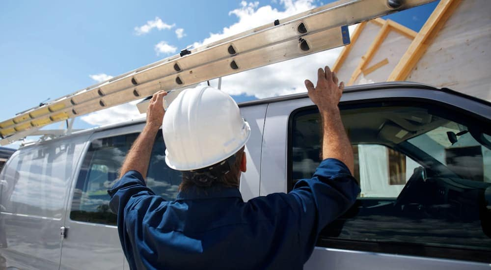 A construction worker is putting a ladder on the top of his 2019 Chevy Cargo van, one of the popular Chevy vans for sale in Cincinnati, OH.