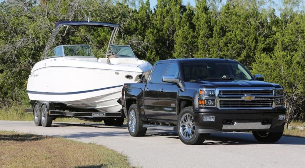 A black Chevy Silverado is towing a boat near Louisville.