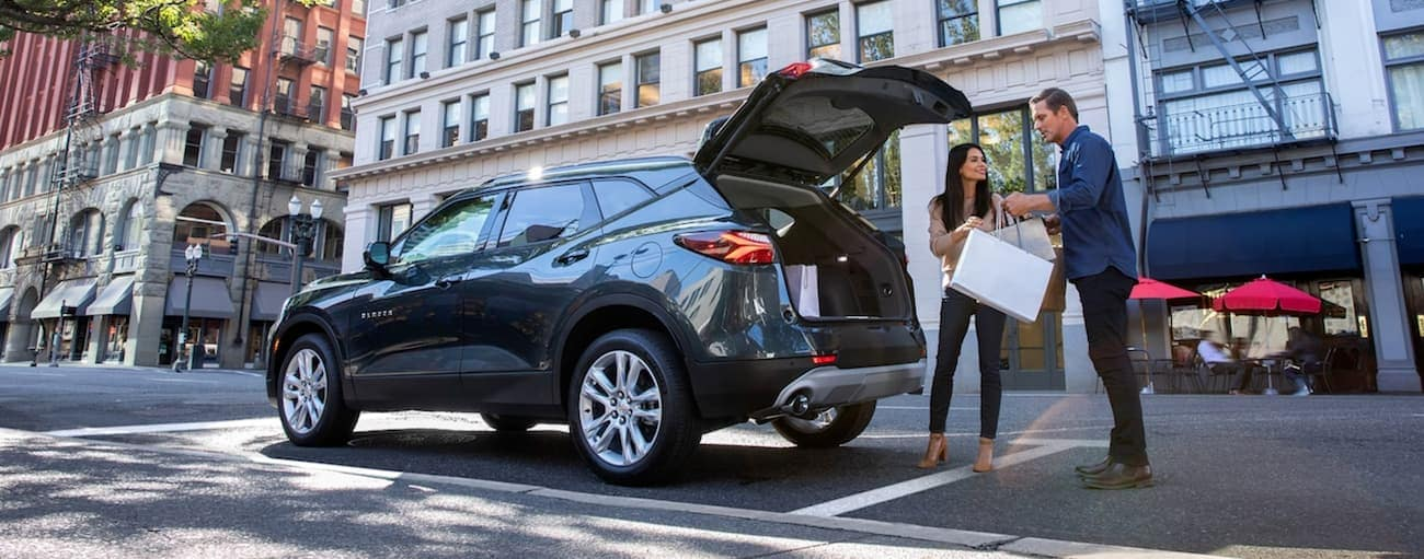 A couple is loading bags into the back of a graphite 2019 Chevy Blazer in Cincinnati, OH.