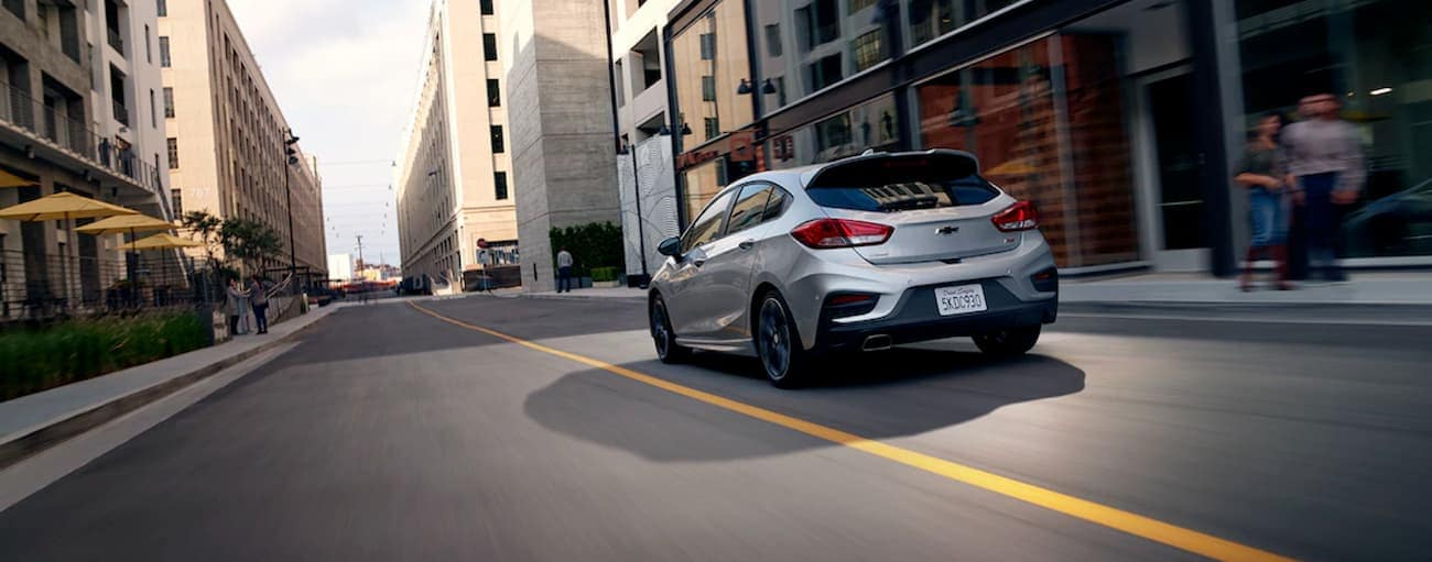 A grey 2019 Chevy Cruze hatchback is driving through the city.