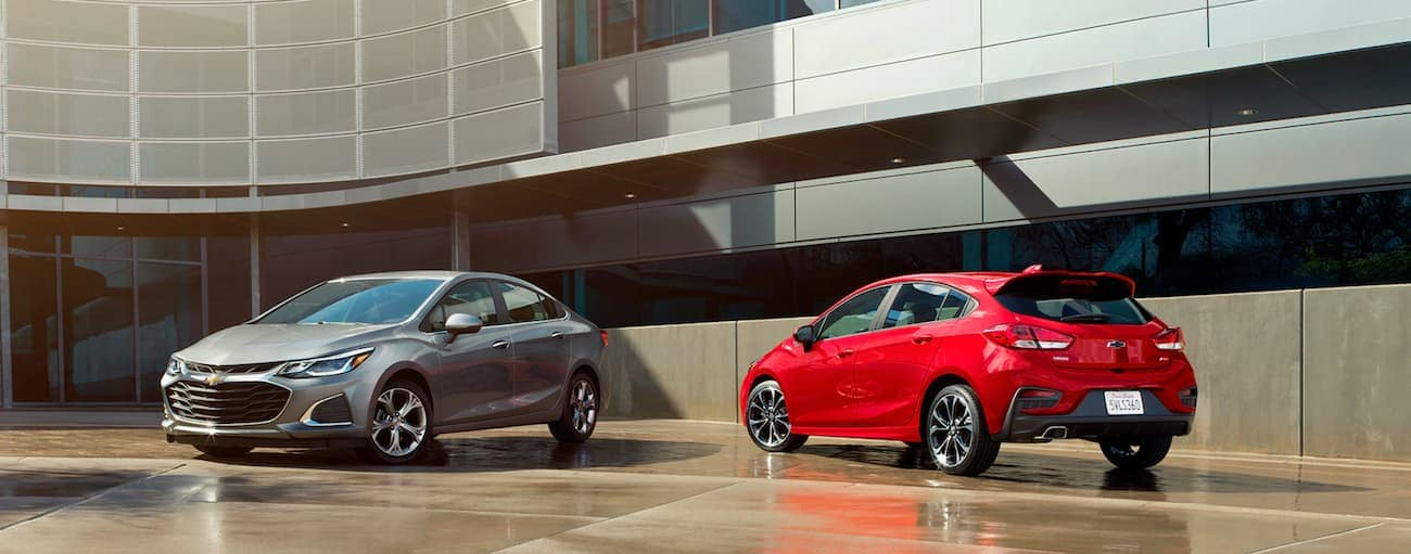A grey 2019 Chevy Cruze is parked next to a red 2019 hatchback outside a glass building near Cincinnati, OH.