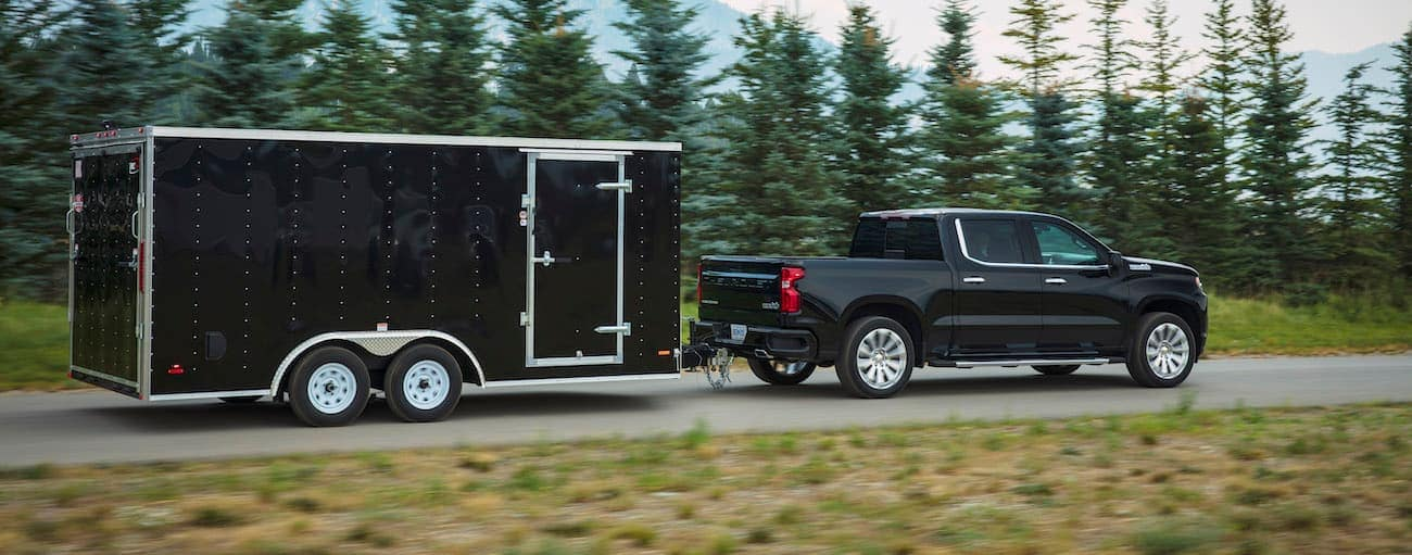 A black 2019 Chevy Silverado, which wins when comparing the 2019 Chevy Silverado vs 2019 Toyota Tundra, is towing an enclosed trailer.