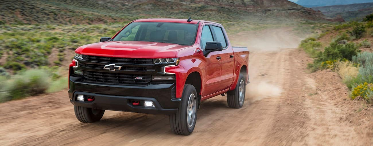 A red 2019 Silverado TrailBoss is driving on a dirt road.