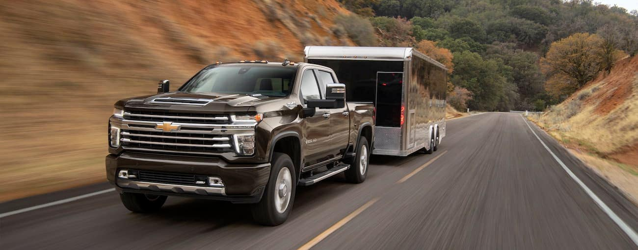 A black 2020 Chevy Silverado 2500HD is towing an enclosed trailer uphill.