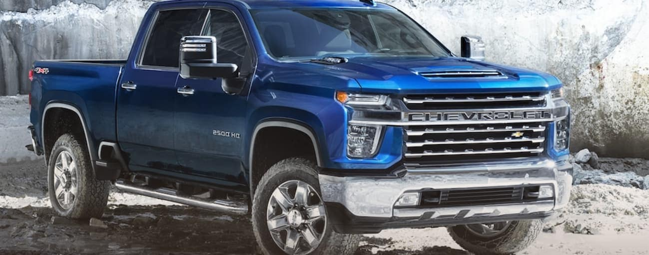 A blue 2020 Chevy Silverado 2500HD is parked in front of large rocks.