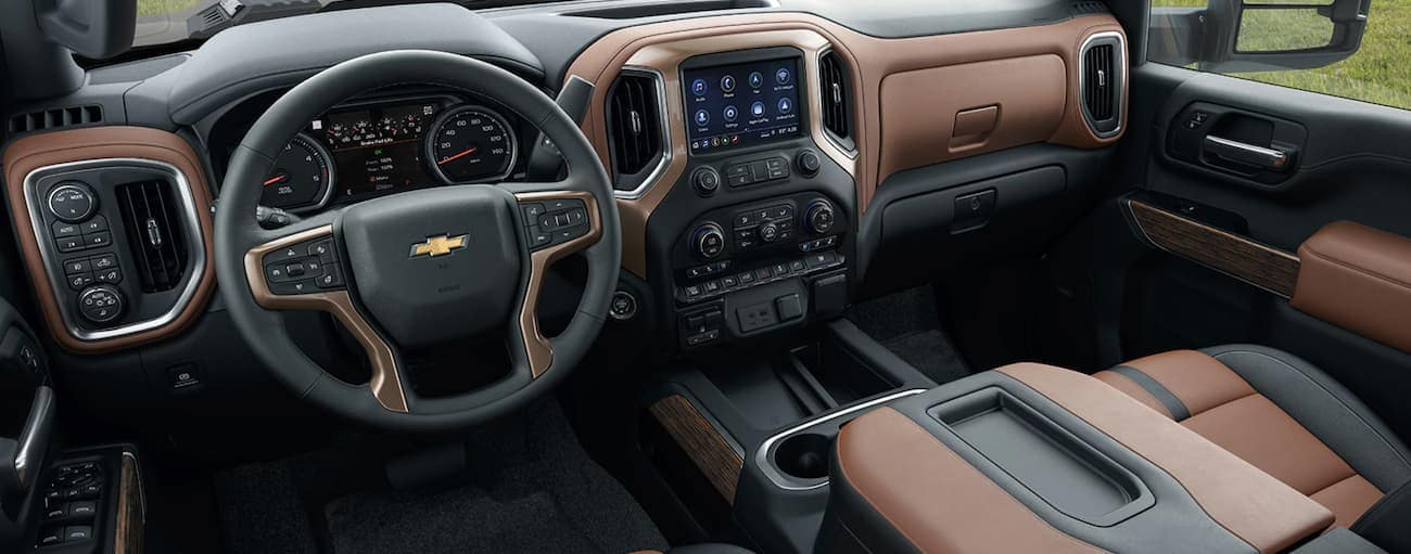 The front brown and black leather interior of a 2020 Chevy Silverado 2500HD is shown with an infotainment system and drivers display.