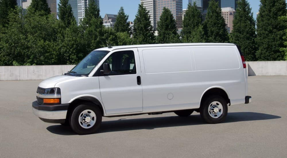 A used white Chevy van for sale is parked with city buildings in the background.