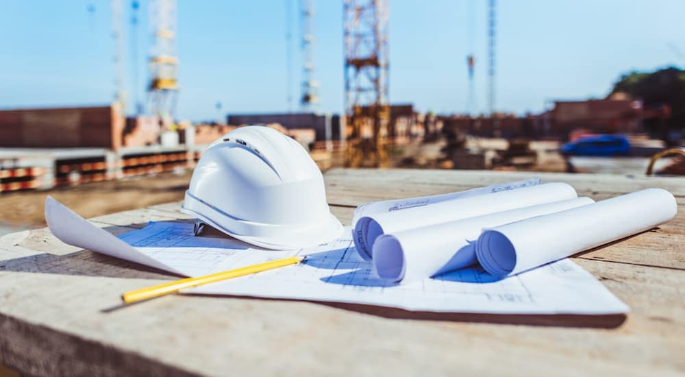 Building plans and a hard hat are shown with construction in the background.