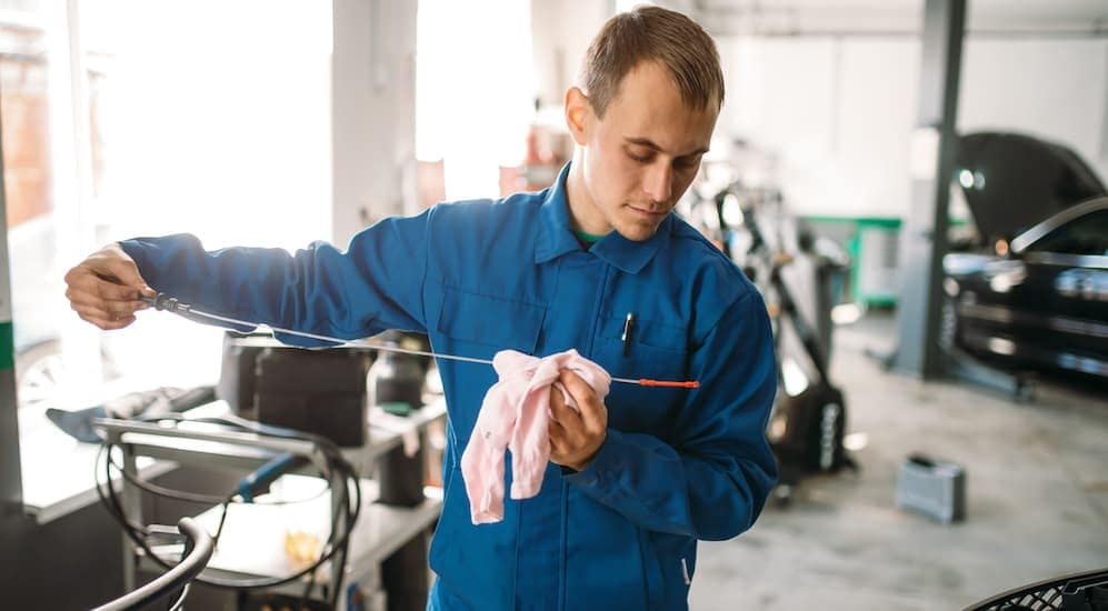A mechanic is checking engine oil levels in a garage in Cincinnati, OH.