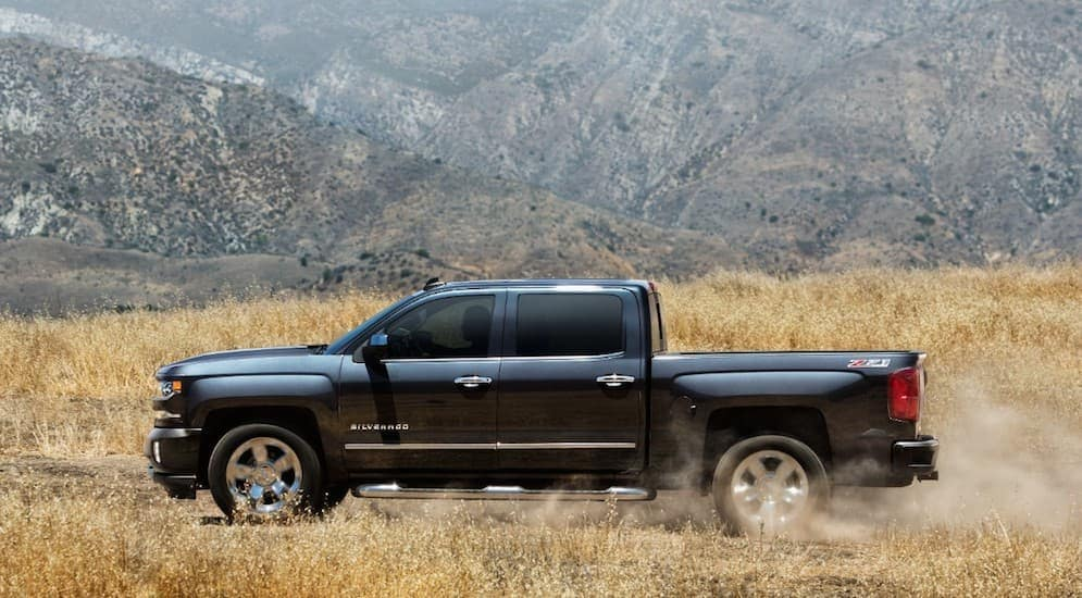 A 2018 black Chevy Silverado is shown with truck accessories, driving on a dirt road with mountains in the background.