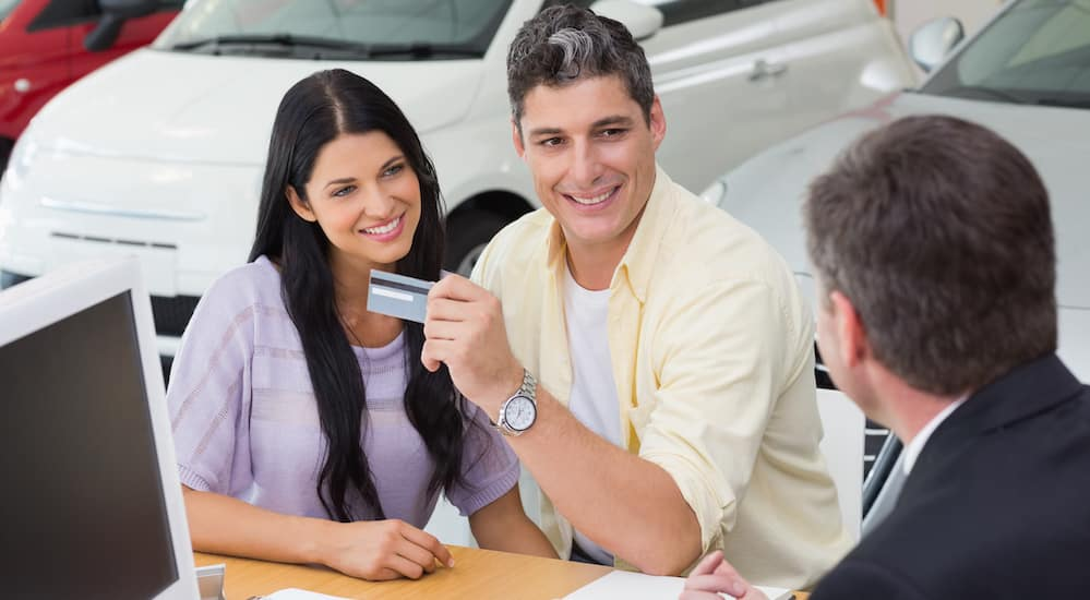 A smiling couple is ready to pay for the used car they just picked out at the dealership in Cincinnati, OH.