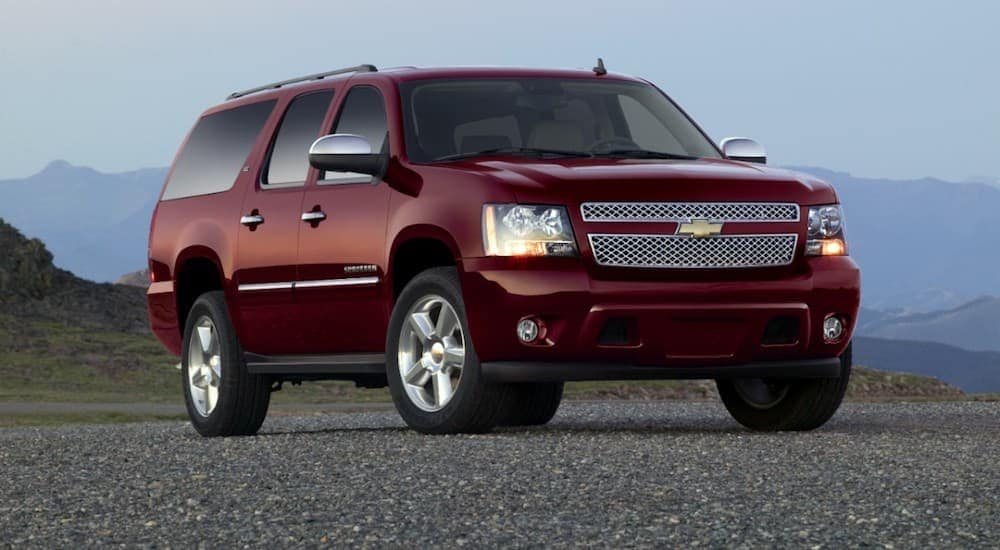 This is a 2013 red Chevy Suburban parked on pavement with mountains in the background.