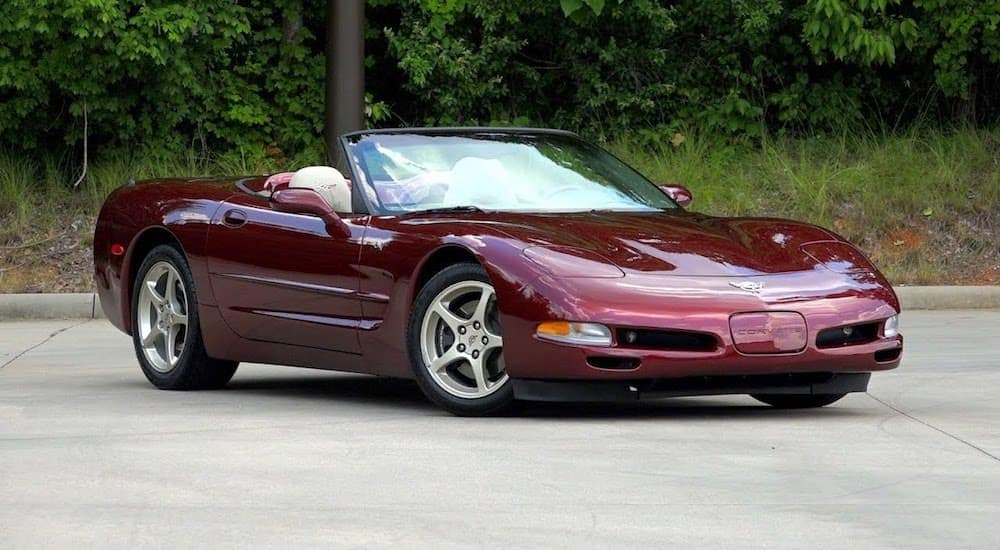 This is a red 2003 Chevy Corvette convertible parked on pavement with trees in the background near Cincinnati, OH.
