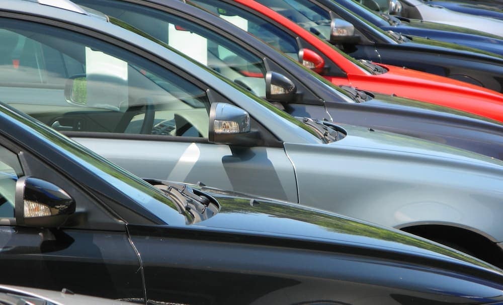 A row of different colored used cars is shown.