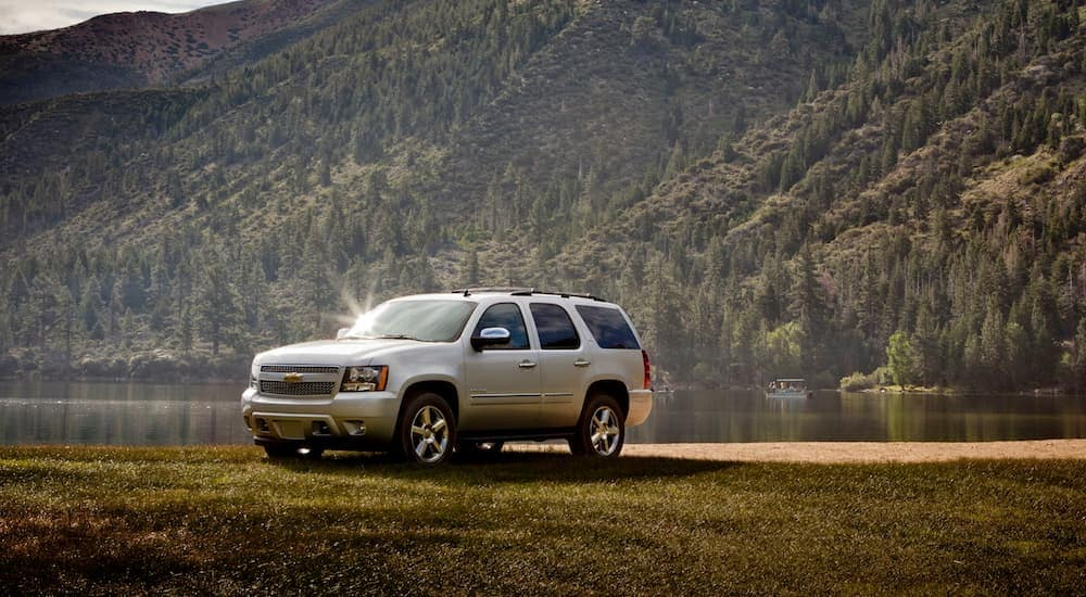 A 2012 Silver Chevy Tahoe is shown parked near a lake in the woods with mountains behind it.