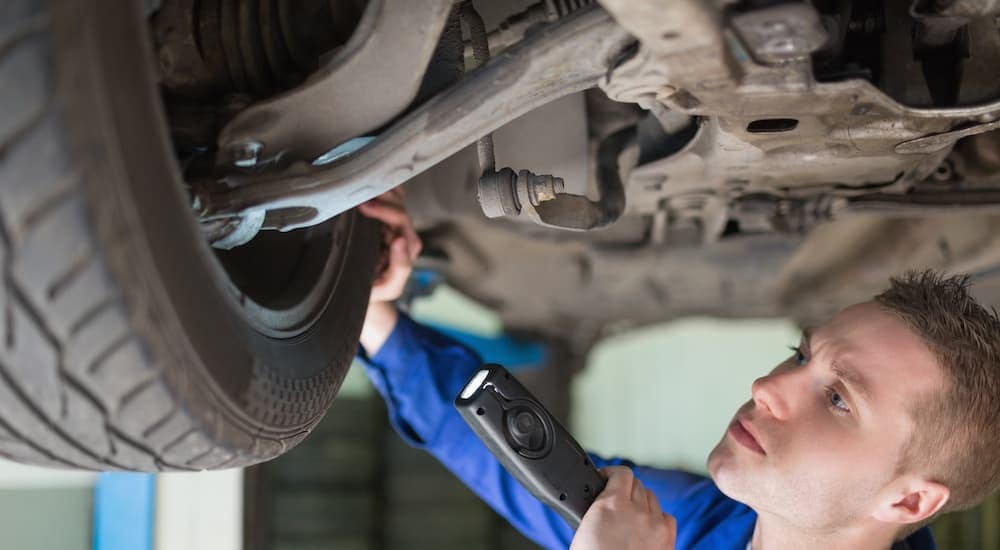 This is a mechanic under a car looking at the wheel assembly.