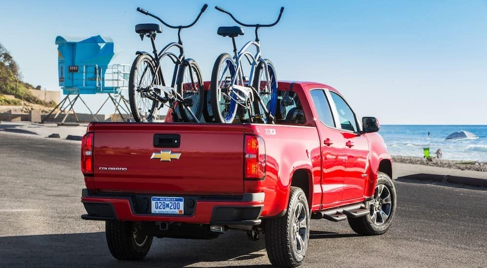 A red 2018 Chevy Colorado is shown with 2 bikes in the bed near water in Cincinnati, OH.
