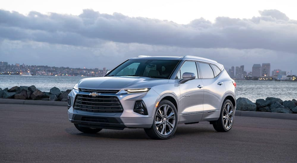 A 2019 silver Chevy Blazer is parked in a parking lot, with a city skyline in the background.