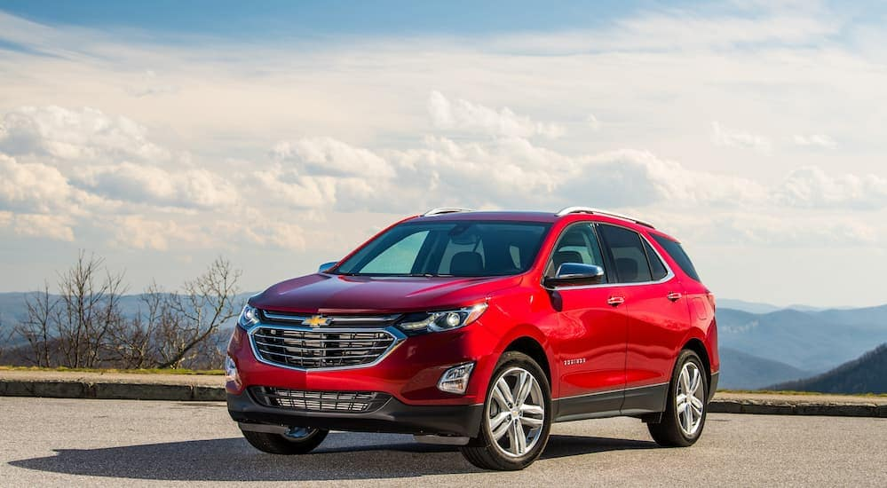 A 2019 Chevrolet Equinox is shown parked in a parking lot with a cloudy blue sky in the background. You can find this vehicle by searching for crossovers and SUV's for sale in Cincinnati, OH.
