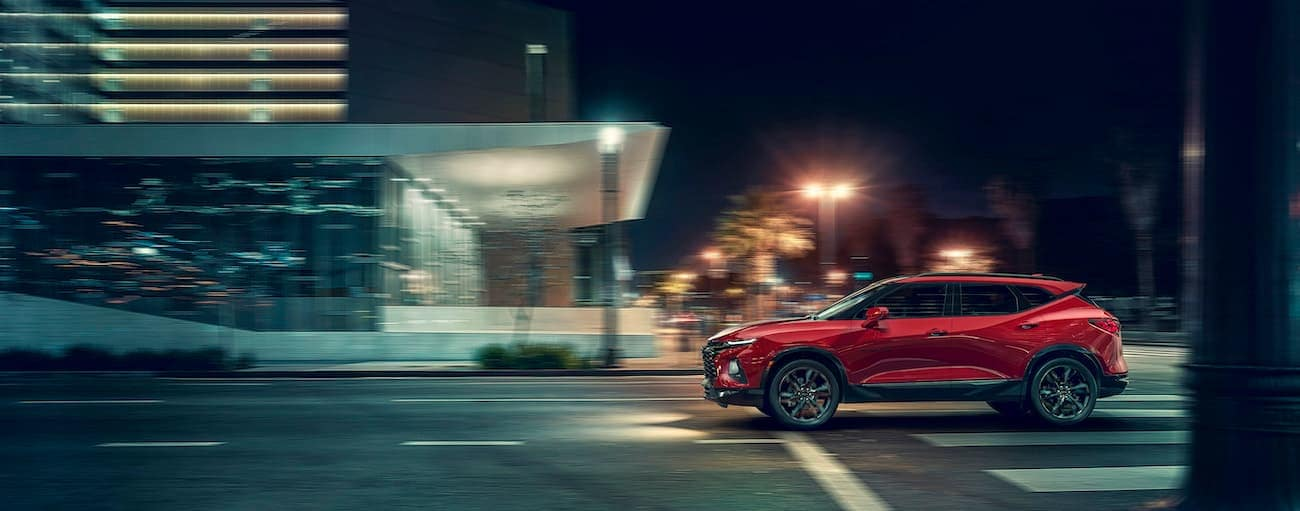 A red Blazer, which wins when comparing performance for the 2019 Chevy Blazer vs 2019 Honda Passport, is driving through an intersection near Cincinnati, OH at night.