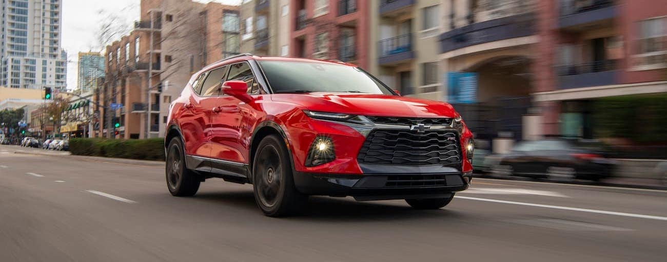 A red 2019 Chevy Blazer, which wins when comparing the 2019 Chevy Blazer vs 2019 Nissan Murano, is driving downtown in Cincinnati, OH.