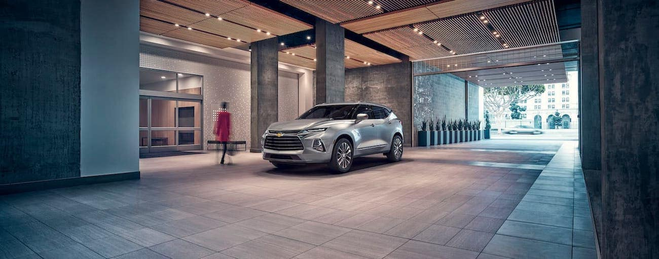 A silver 2019 Chevy Blazer is parked under cover in front of a modern building  near Cincinnati, OH.